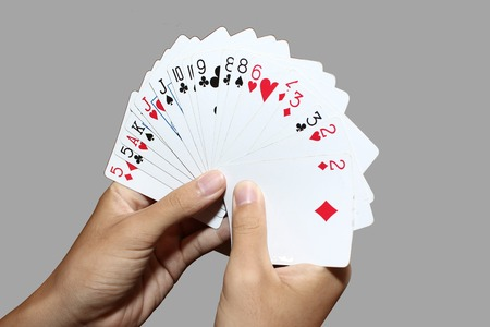 Playing cards in hand isolated on gray background
