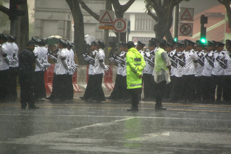 SINGAPORE - Mar 29: Singapore, Public standing in a downpour, line up the streets to bid farewell to Mr. Lee Kuan Yew after his cortege pass by during the funeral procession, on Sunday, 29 March 2015.
