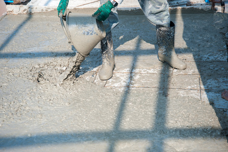 damp proofing: Worker pouring cement in construction site Stock Photo