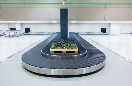 empty baggage carousel in airport hall with granite floor-Baggage claim area, transporter belt