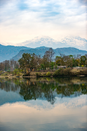 phewa: Lake Phewa in Pokhara, Nepal, with the Himalayan mountains in the background, including Machhapuchhre and Annapurna Stock Photo