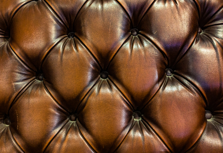 sitting on sofa: Luxury and grungy background of classic shabby leather texture of a couch with leather buttons Stock Photo