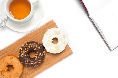 tae: Delicious donuts with icing, book and tae in wood plate isolated on white Stock Photo
