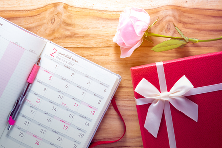 Gigt box with calendar book , rose flower and white ribbon. Valentines day simbols on a wood background