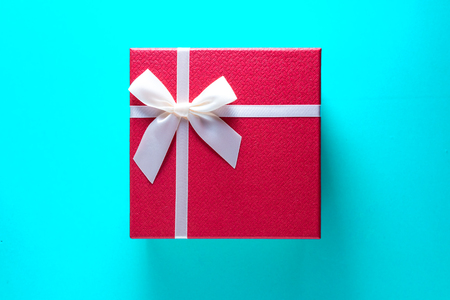 Gigt box with and white ribbon. Valentines day simbols on a blue table background Stock Photo