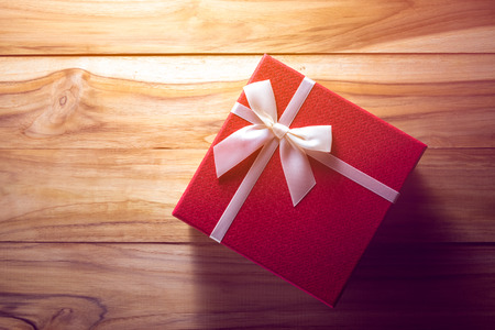 Gigt box and white ribbon. Valentines day simbols on a wood background Stock Photo