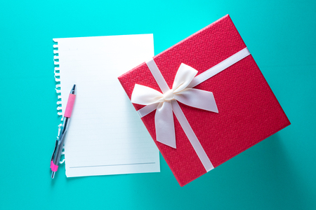 Gigt box with paper card and white ribbon. Valentines day simbols on a blue table background