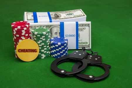 Stack of cash with poker chips and handcuffs