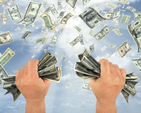 Wealth idea in a metaphor of rain of dollars. The hand holds some dollars. Stock Photo
