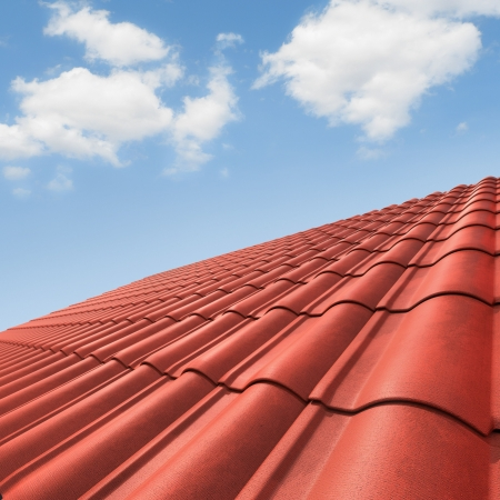 roof tiles: View of red roof tiles and cloudy sky on the background. Stock Photo