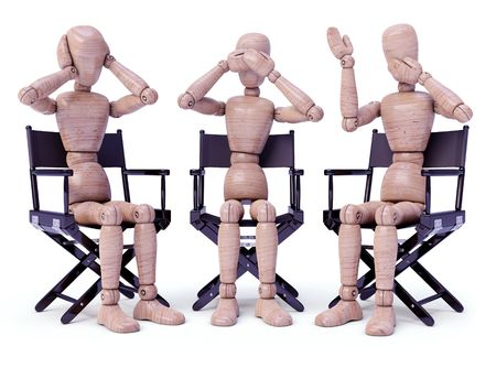 wise: Three wooden dolls sitting doing bodily gestures. Concept of the three wise monkeys. Stock Photo