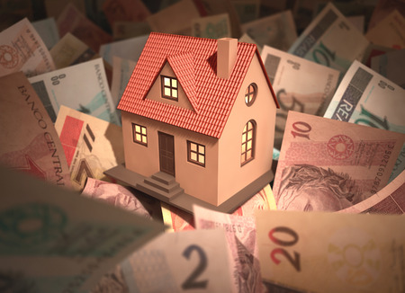 Small house surrounded by Brazilian money (Real) with deph of field. Stock Photo - 26019135