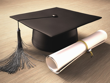 graduation cap and diploma: Graduation cap with diploma over the table. Clipping path included.