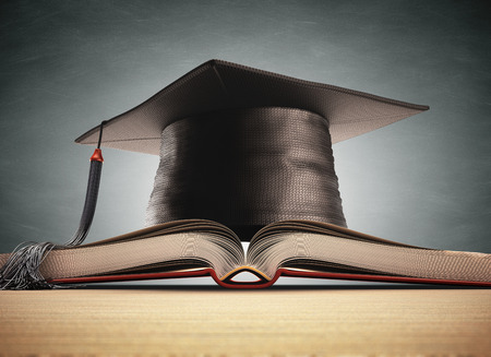 master degree: Graduation cap over the book with blackboard on background. Clipping path included.
