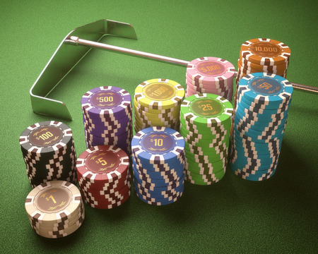 Colorful chips on a green table. Concept of casino and gambling. Clipping path on the chips.