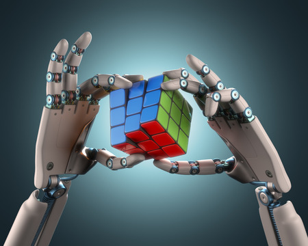 Robotic hand holding a colorful cube. Clipping path included.