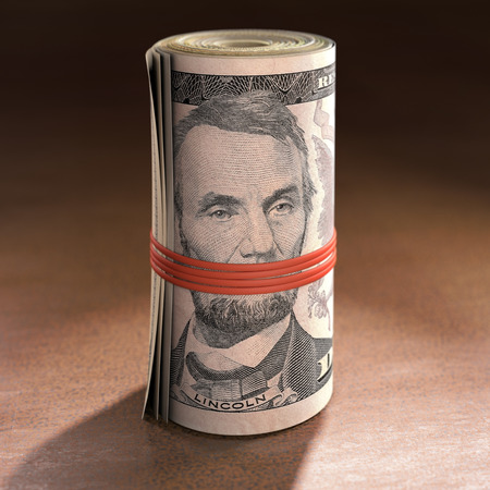 Money roll with elastic gagging the mouth of Abraham Lincoln. Stock Photo