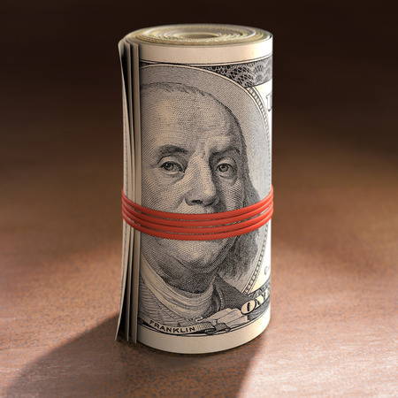 benjamin franklin: Money roll with elastic gagging the mouth of Benjamin Franklin. Stock Photo