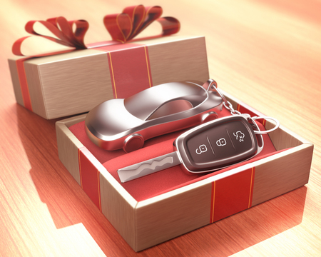 Car key inside a gift box with a red ribbon tied up on the cover. Depth of field with focus on the key button. Stockfoto