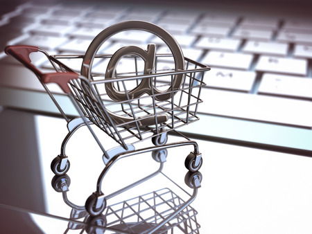 At sign, inside of the shopping cart on a laptop. E commerce concept. Depth of field with focus on At sign. Stockfoto