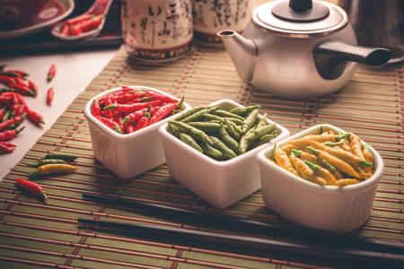 Red, green and yellow peppers on an oriental style table. Depth of field with focus on center of the image.
