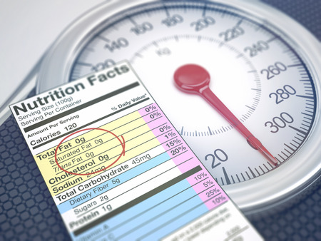 total loss: Weight scale with nutrition facts. Depth of field with focus on fat information.