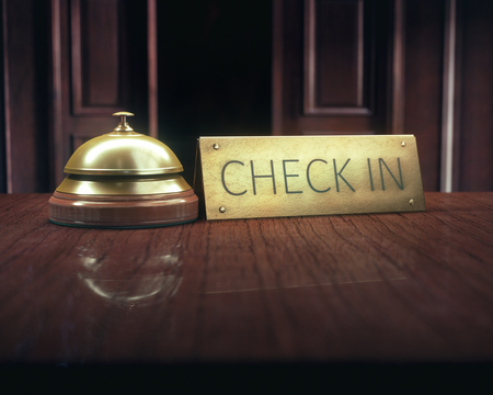 Vintage bell with check in message on the wooden desk of the lobby service.