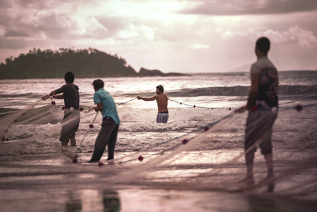 Ilha Do Mel, Paraná, Brazil - June 3, 2017: Native fishermen from Ilha do Mel (Honey Island) pulling the net with fish, for the Feast of the Mullet. Banco de Imagens - 80067646