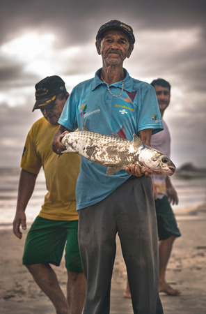 Ilha Do Mel, Paraná, Brazil - June 3, 2017: Fisherman native to Ilha do Mel (Honey Island), holding a mullet. Editorial