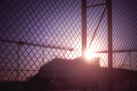 eventide: Sunset behind a rusty wire fence.