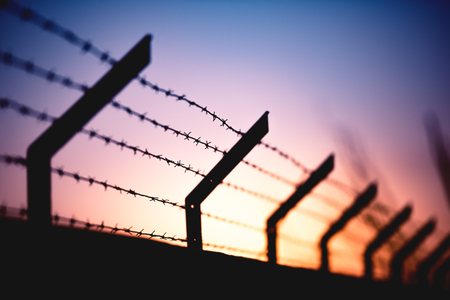 eventide: Wall with barbed wire and a sunset in the background. Stock Photo