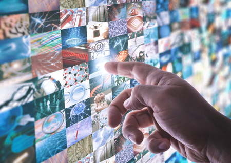 The hand touches the touchscreen led panel with various images about technology and science. Stock Photo