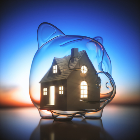 Piggy bank of glass, with a miniature house lit inside. Concept of saving money for the purchase of a new house.