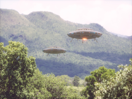 Two unidentified flying objects over a forest with trees and mountains behind. Stock Photo