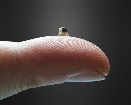 Kleiner Mikrochip an der Fingerspitze. Finger, der einen miniaturisierten Mikrochip hält. Technologiekonzept und Entwicklung der Informatik.