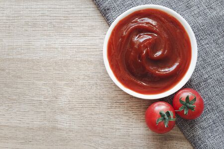 Tomato ketchup sauce in ceramic bowl on placemat with tomatoes over wooden background. Archivio Fotografico - 142422226