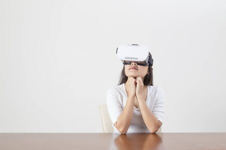Young woman acting while wearing VR device or virtual reality glasses over white background.