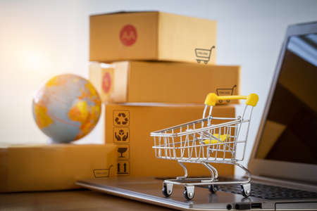 Shopping cart or trolley on a notebook computer placed in front of the parcel box for delivery to customers. Commercial transactions conducted electronically on the Internet for distance selling.