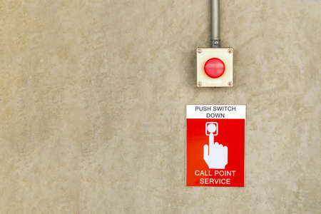 fire alarm call point service sign label with red color push button switch on cement wall. Banque d'images