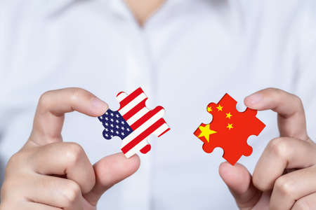 Hand holding USA and China jigsaw puzzle piece, Symbolic concept about trade war between USA and China. Banque d'images