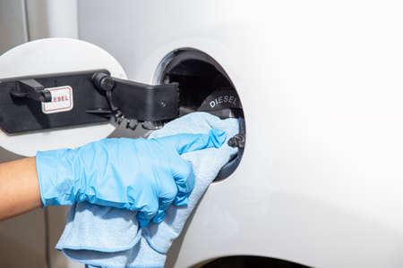 Hand are wearing rubber gloves and use microfiber cloth to clean the tank cap. Car interior cleaning concept