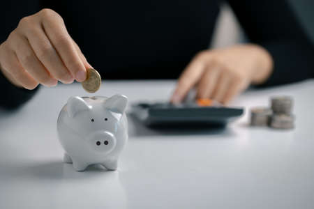 Hand putting coin to piggy bank and using calculator, Saving money and calculating financial.
