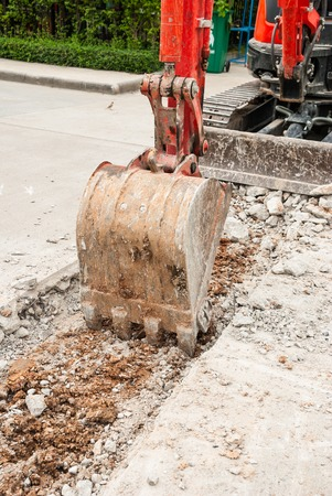 Excavator breaking concrete road surface. Shows part of the excavator bucket. photo