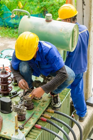 essentially: Nonthaburi, Thailand - September 28, 2015 : Electrician preparing an oil change a power transformer of condominium. This activity is according to the specified period.