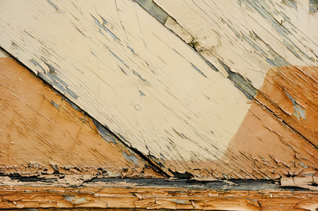 Texture of very old badly scratched wooden planks with cracked and peeling yellow and brown paint