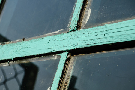 Old window with unwashed windowpane and chapped window frame painted green close view