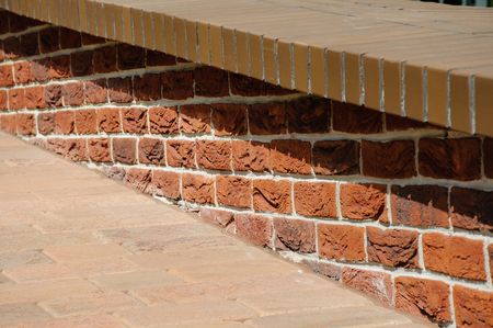 Low parapet made of red and dark red bricks beside brick pavement at summer day
