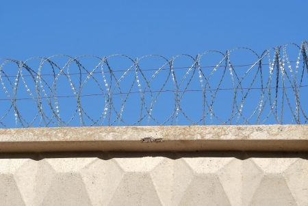 robben island: Reinforced concrete fence with barbed wire against the sky