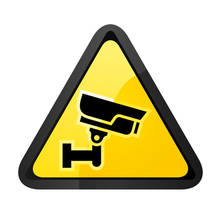 Black surveillance camera on a yellow triangular shape