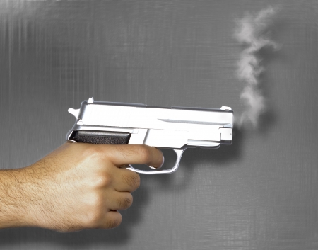 Hand shooting gun and smoke on white background photo